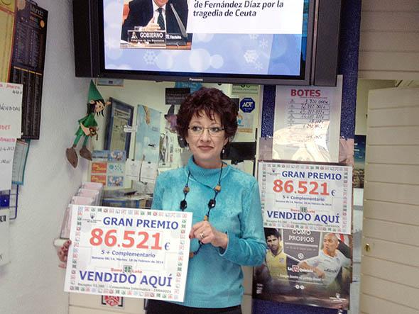 Ana Carmen Puchan, presidenta de la Asociación de Zaragoza, da un premio en la Bonoloto